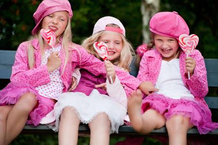 paleta de caramelo: Felices los ni�os tengan ropa de color rosa y un lollipop Foto de archivo