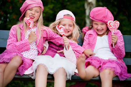 Happy children having pink clothes and a lollipop Stock Photo - 5315165