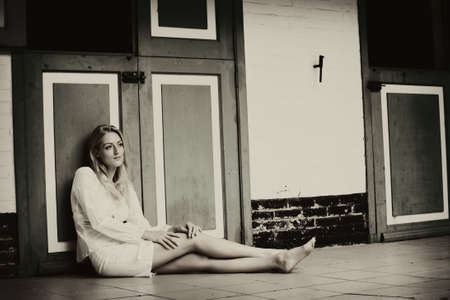 desaturated: Blond beauty in white sitting at the floor against the stable doors. Stock Photo