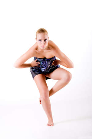 highfashion: Blond model in blue dress balancing on one leg. Usable fot fashion, high-fashion, yoga, health and beauty, dieting, statements and others.