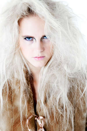 studioshot: Model with wild white hair giving the viewer a fierce and agry look. Usable for health and beauty, cosmetics, love, hate and emotional issues. Stock Photo