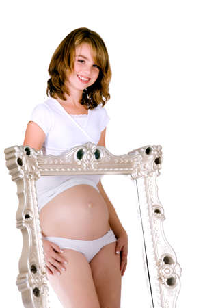Girl behind a mirror wyhile a reflection of a pregnant woman is in it.  Made in a studio environment on white background  photo