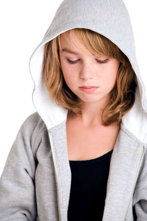 Girl in hooded sweater looking a little angry at you.  Made in a studio environment on white background  photo