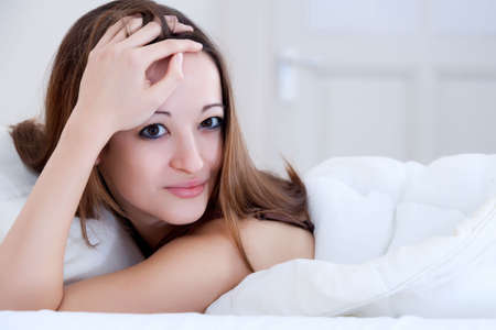 Beautiful woman in a bedroom resting and relaxing photo