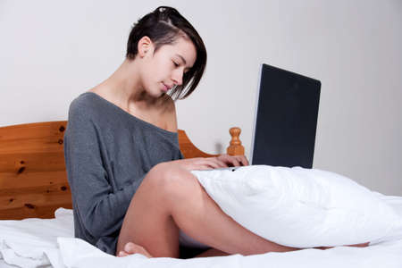 etnic: Young mult etnic woman sitting on her bed with a notebook
