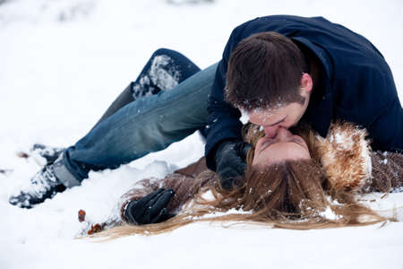 couples hug: lovers being passionate lying in the snow