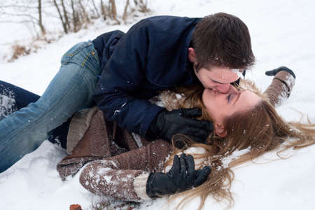 young couple hugging kissing: couple making out in the snow