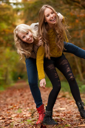 twin sister: 2 girls are having fun in the forest Stock Photo