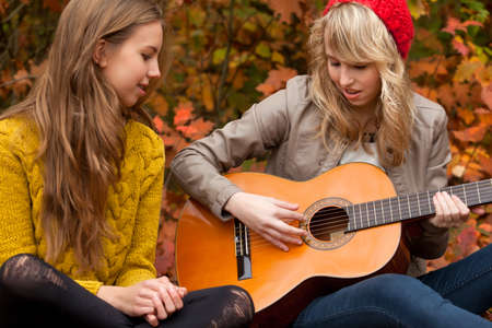 girl playing guitar: 2 girls are having fun in the forest Stock Photo