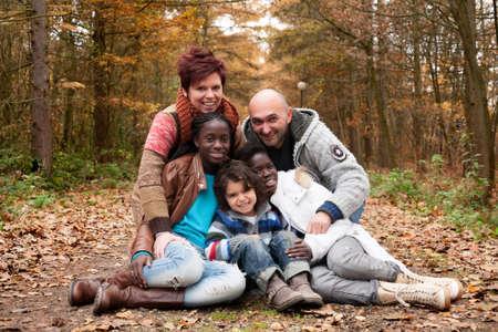 Famiglia felice con i bambini adottivi nella foresta