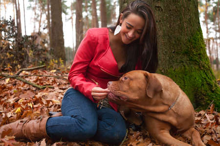 Young woman is having fun with her dog in the forest Stock Photo - 17414210