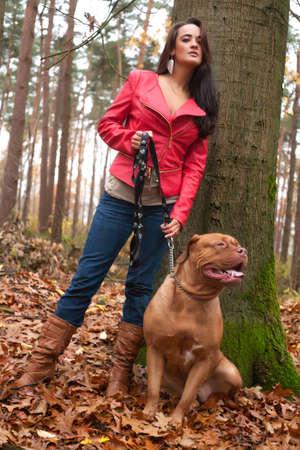 Jonge vrouw met plezier met haar hond in het bos