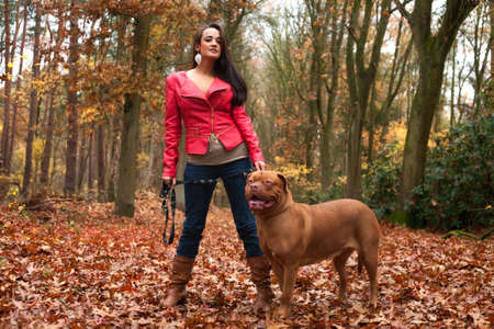 Young woman is having fun with her dog in the forest Stock Photo - 17414219