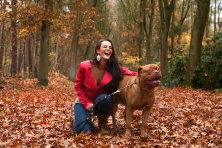 Young woman is having fun with her dog in the forest photo