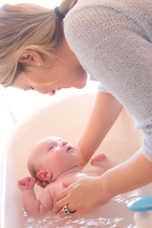 baby bath: Happy young parents and their little baby