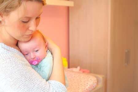 babyroom: Happy young parents and their little baby