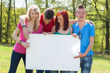 Four teenagers in colored shirts and a white board Stock Photo - 19908672