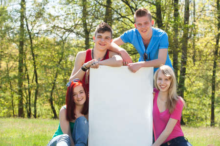 Four teenagers in colored shirts and a white board Stock Photo - 19908679
