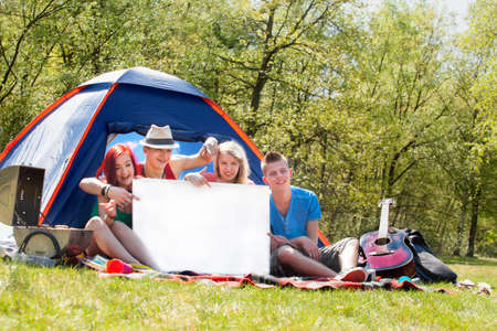 bivouac: Four teenagers in colored shirts on the camping with a white board