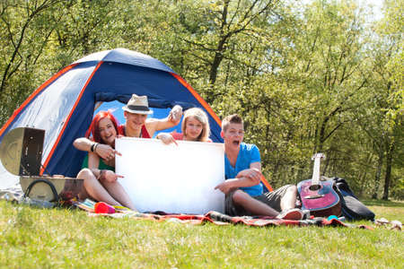 Four teenagers in colored shirts on the camping with a white board Stock Photo - 19908656
