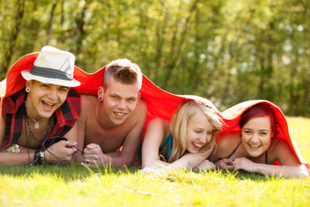 Four teenagers are hiding under a blanket photo