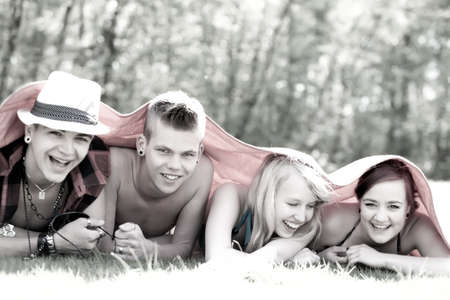 Four teenagers are hiding under a blanket Stock Photo - 19908674