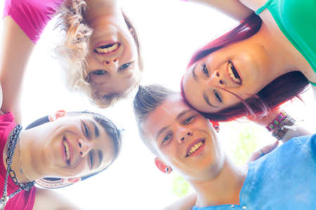 Four teenagers are having fun and looking downstrairs photo