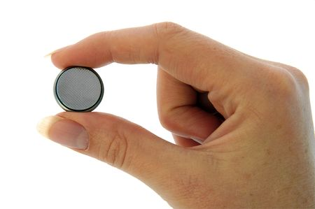 nimh: An isolated image of a small watch battery held between fingers - negative side