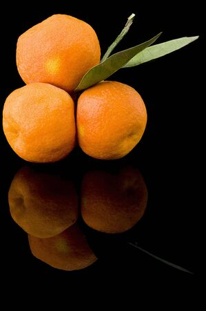 An isolated image of three fresh oranges on a black background Stok Fotoğraf