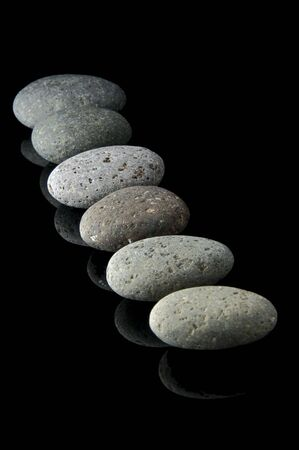 unbalanced: An isolated to black image of 6 stones