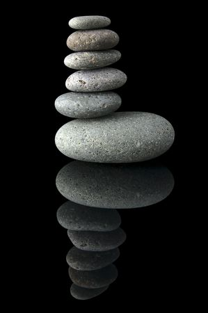 An isolated to black image of an unblanced stack of stones photo