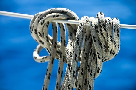 A photo of a rope tied off to a boat stay, against the blue of the sea Stock Photo - 5145935