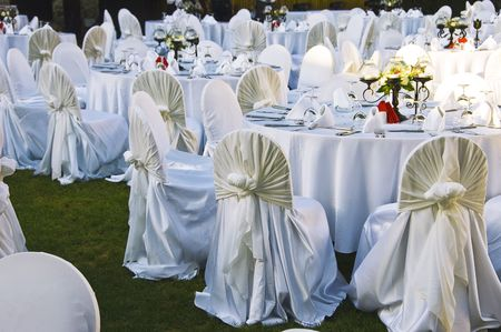 wedding table setting: Wedding Chairs and covers at an outdoor wedding