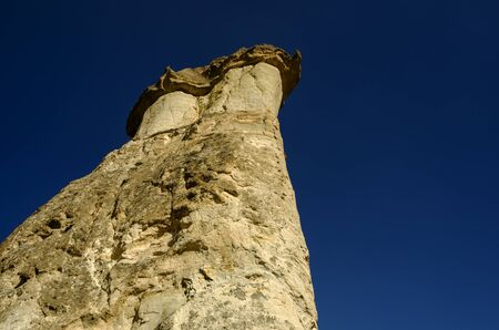 erode: A lone fairy chimney against a blue sky