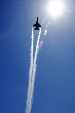fighter jet passing directly overhead into the sun photo