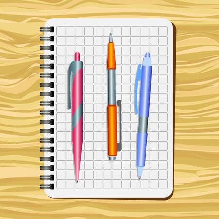 Notebook,  red  pen, orange pen and blue pen on a wooden table.