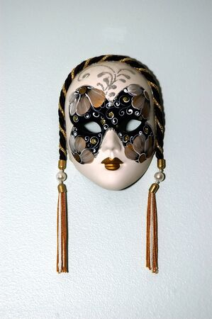 Female Venetian mask used as a wall hanging against a soft light photo