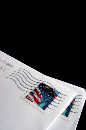 Postage Stamps on a white envelope delivered by a Postman