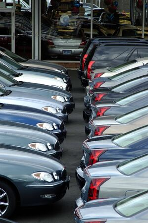 Two rows of car stacked at a locak car dealer