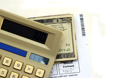 payable: Calculator, bill, pen and cash against a white background Stock Photo