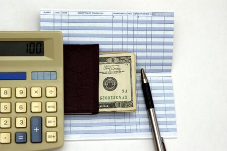 payable: Calculator, check book, transaction register and a pen against a white back ground