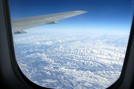 windows frame: Looking snow clad mountains through the plane window Stock Photo