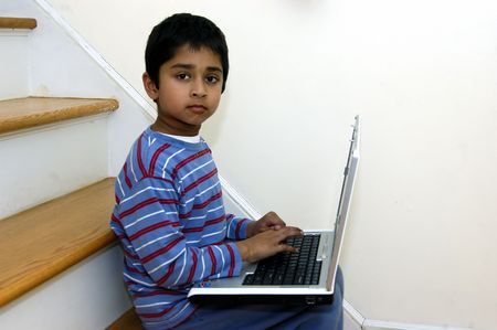 A kid doing his homework using a laptop Stock Photo - 671701
