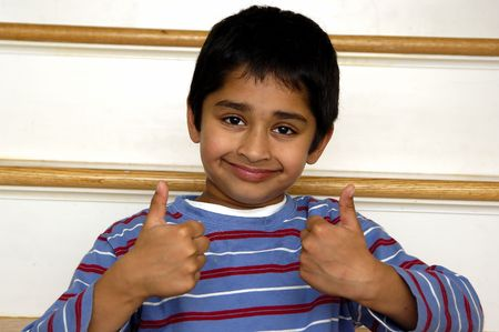 A kid showing double thumbs up with a smile Stock Photo - 671703