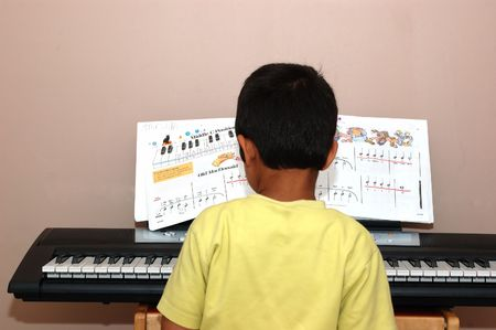 A kid playing the piano with notes written down Banco de Imagens