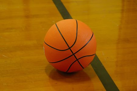 basketball ball on a court - wooden floor with the reflection of the ball on the wood photo