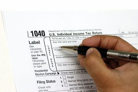 taxable: Filing a tax return. Pen and check book against the tax form Stock Photo