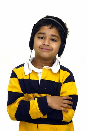 A kid listening to music using headphones on a white background