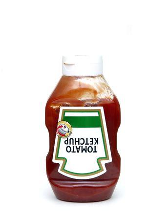 potherb: Una botella de la salsa de tomate aislada contra una tierra de la parte posteriora del blanco Foto de archivo
