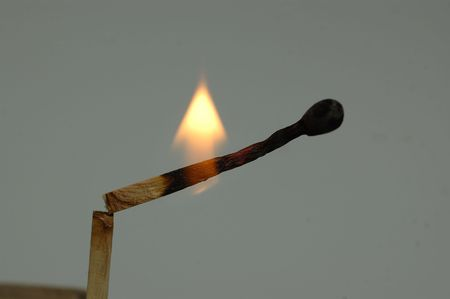 A mburning matchstick isolated against a gray background